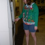 Young woman uses an atm in an ugly Christmas sweater
