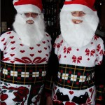couple wearing matching ugly christmas sweaters and santa beards