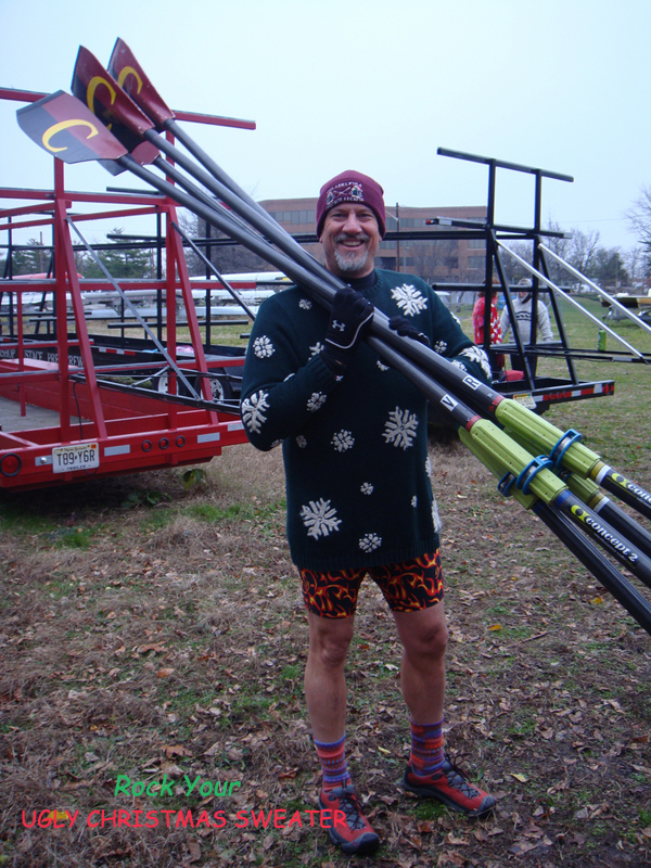 Photo of man in ugly Christmas sweater holding rowing oars