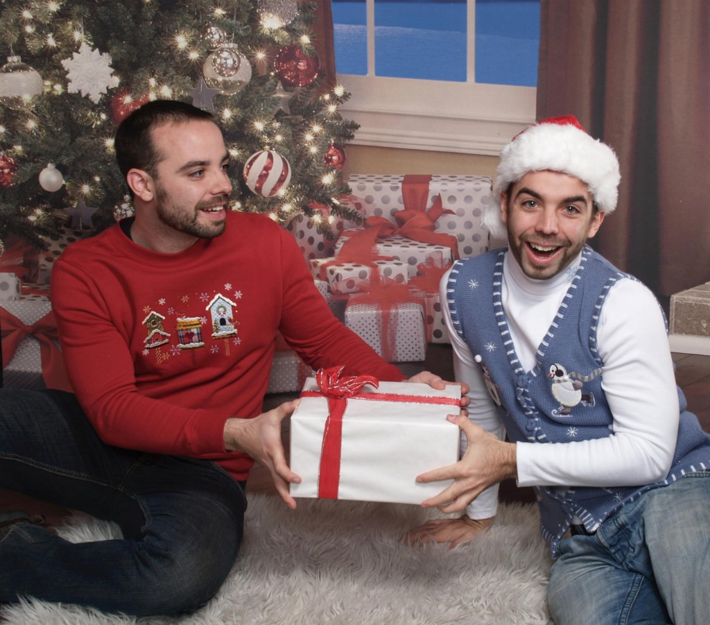 Twins fight over a present under tree in ugly Christmas sweaters